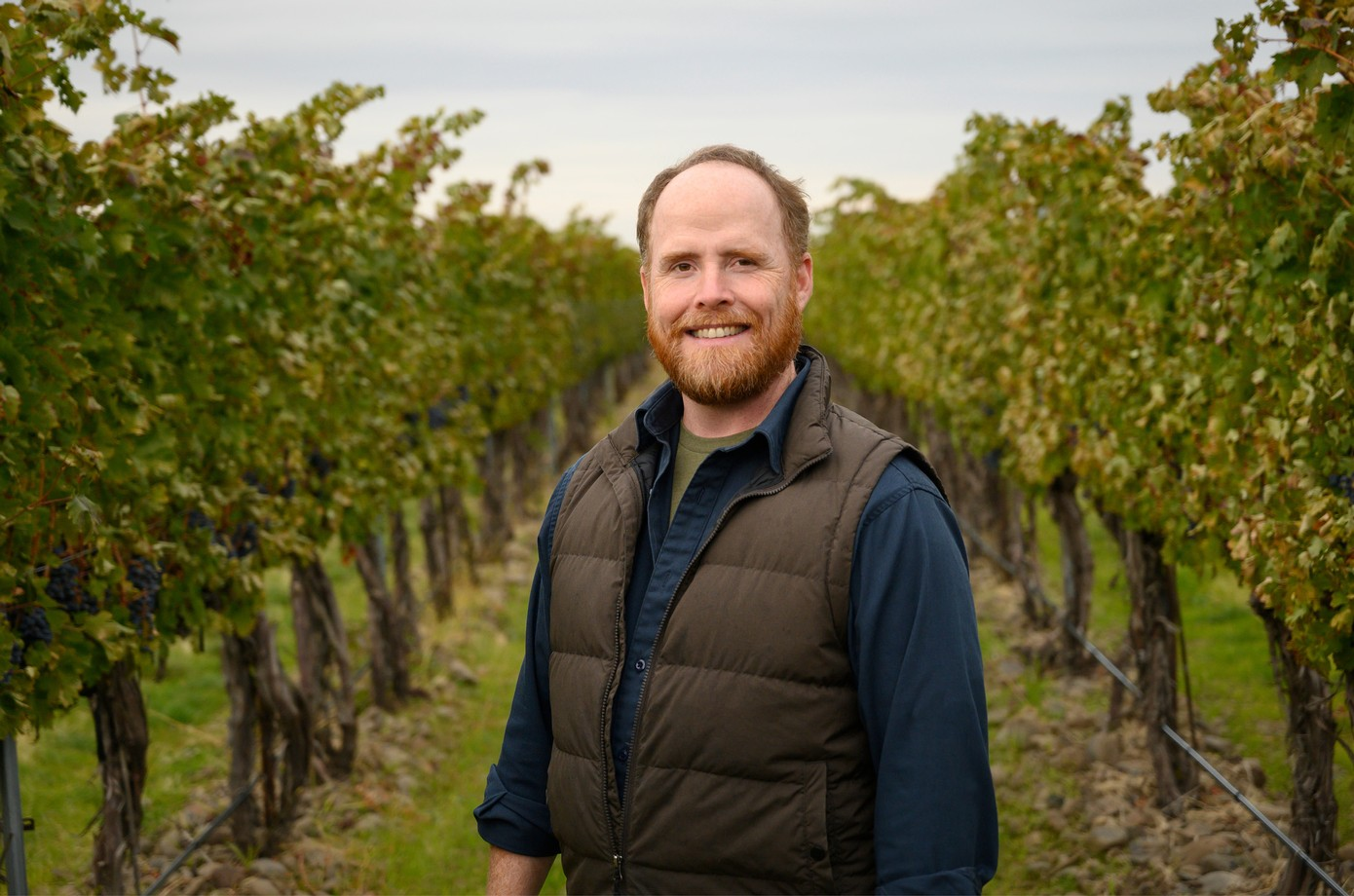 Marc Leahy, winemaker, in vineyard with rocks